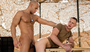 Sergeant Sean Zevran comes up behind his subordinate, Brandon Evans, and clutches his ass