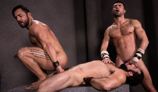 Tattooed warriors Bruno Bernal and Ian Greene sit and make out although stroking their hard cocks