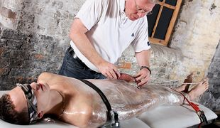 Luke is the restrained victim for Sebastian in this cock stroking session